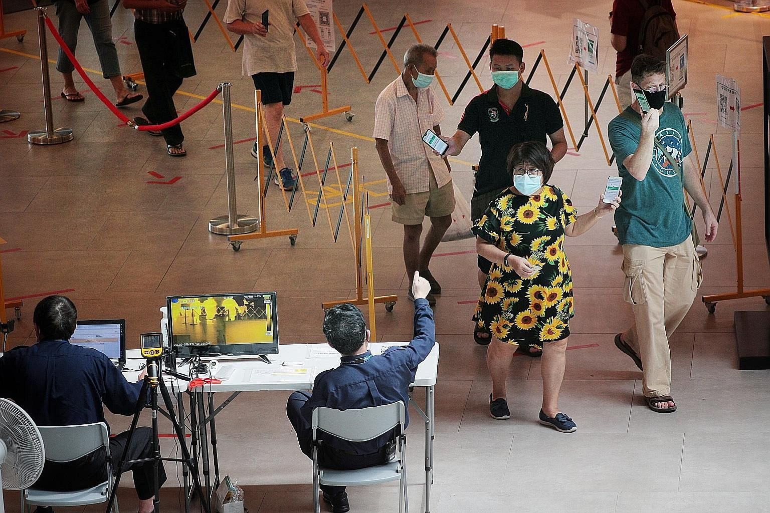 People showing security guards they had checked in using the SafeEntry system as they entered SingPost Centre yesterday. The Health Ministry reminded the public to limit social gatherings to no more than five people and said the behaviour of the man