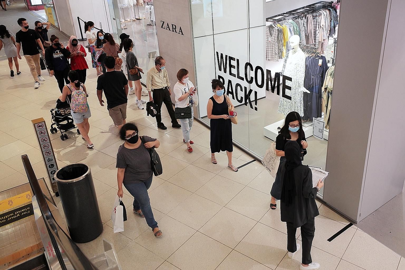 Shoppers queueing to enter a store at VivoCity mall on Sunday, the first weekend of the reopening of Singapore's economy. The author says that when a country relaxes its restrictions on people's movement, it is inevitable that said country will begin
