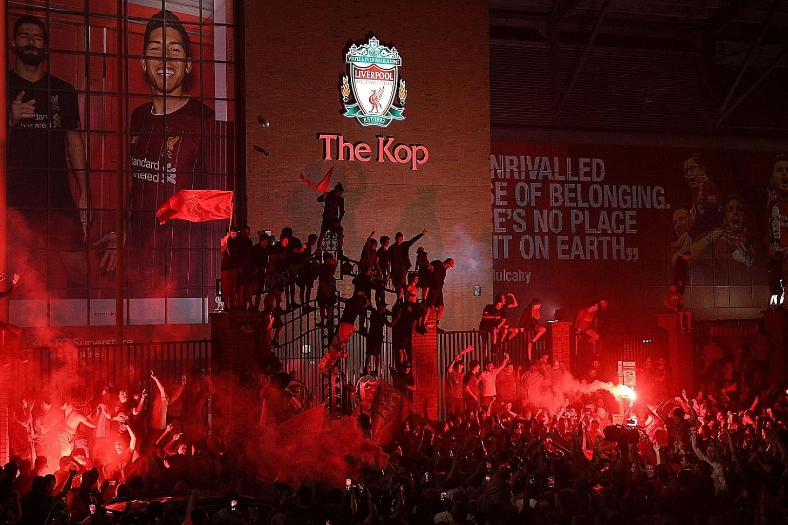 Young Liverpool fans Kendall, five, and Sadie, three, seem to be the only ones observing social distancing as they raise a Premier League trophy placard. But thousands (above) gathered outside Anfield to party within half an hour of the Reds' coronation,