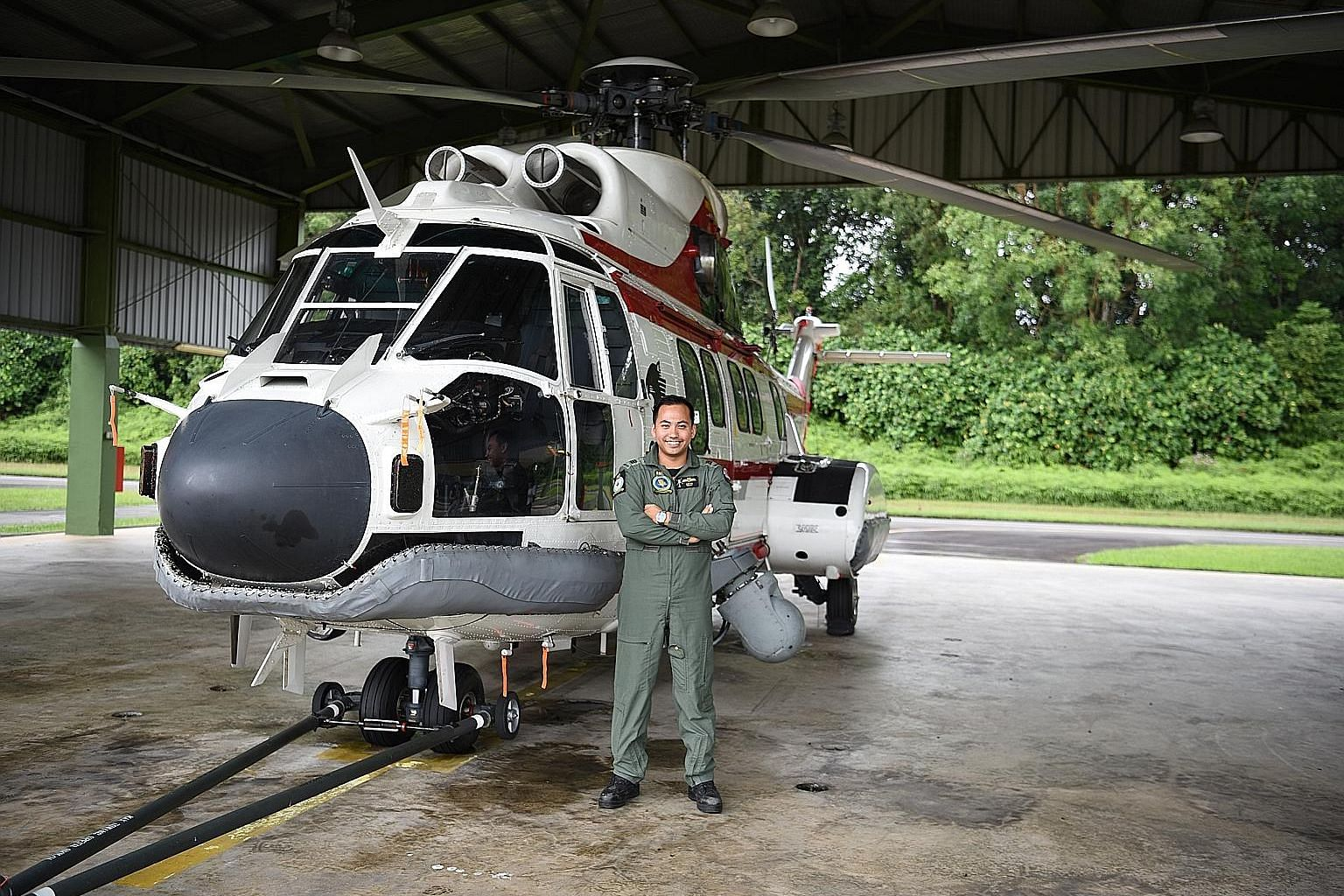 Captain Muhammad Azlan Latiff with the Super Puma helicopter he flies. His promotion to major takes effect on July 1. PHOTO: MINISTRY OF DEFENCE