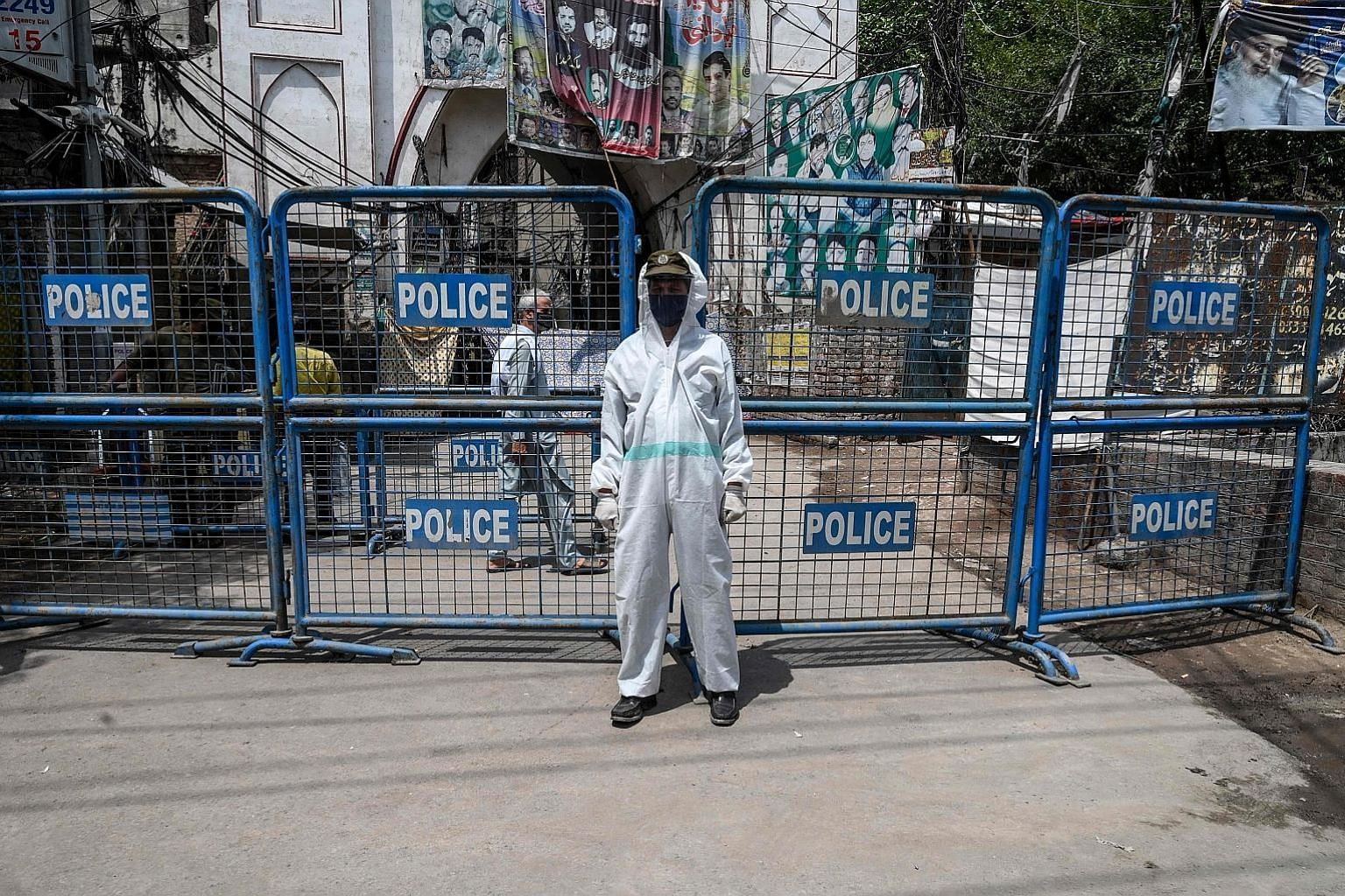 A policeman standing guard at a barricade at a restricted area sealed by the authorities in Lahore, Pakistan, last Thursday. It is evident that, much like the global trend in countries where Covid-19 cases have soared, Pakistan's daily cases and deat