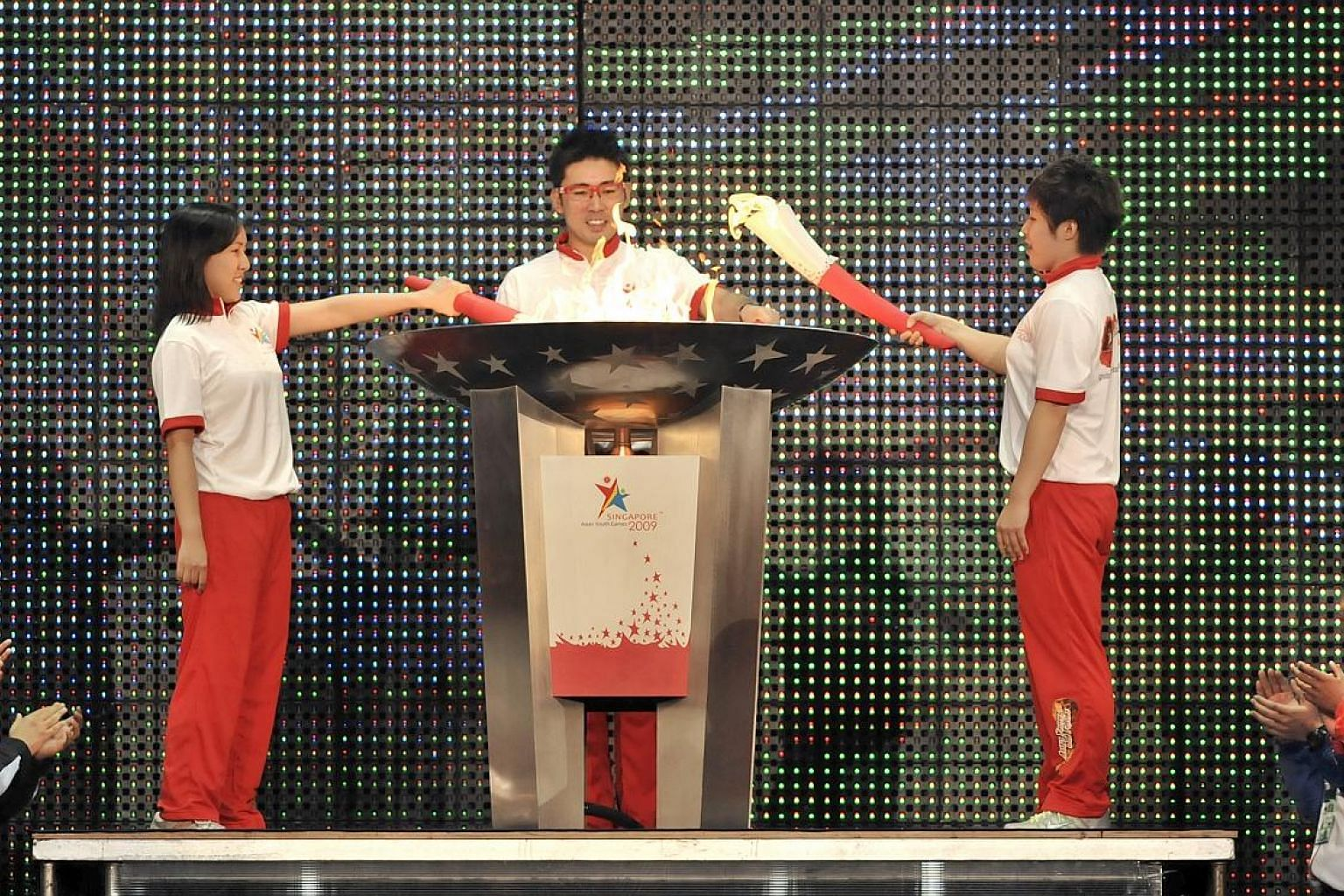 (From left) Shooter Jasmine Ser, bowler Remy Ong and swimmer Tao Li lighting the cauldron at the opening of the Asian Youth Games on June 29, 2009.
