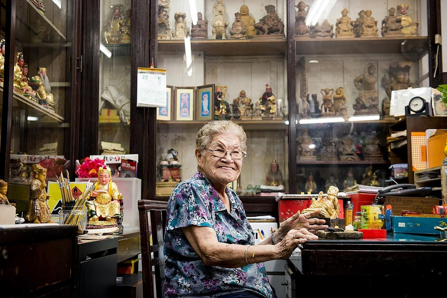 Madam Tan Chwee Lian (above), 89, family matriarch of Say Tian Hng Buddha Shop, carving wooden statues. The 124-year-old Taoist effigymaking shop is organising Design for Deities, an international competition calling for designers to reimagine a 40-year-o