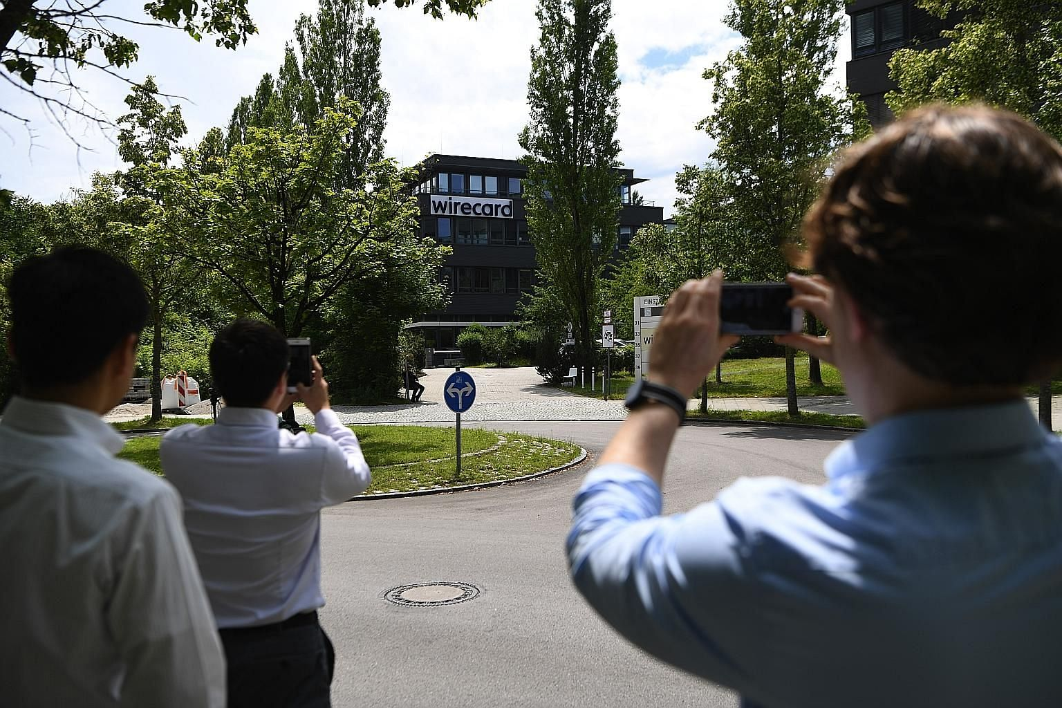 Passers-by taking snapshots of the Wirecard headquarters in Munich, Germany. The company filed for insolvency last Thursday, after almost €2 billion (S$3.13 billion) went missing from its accounts. PHOTO: BLOOMBERG