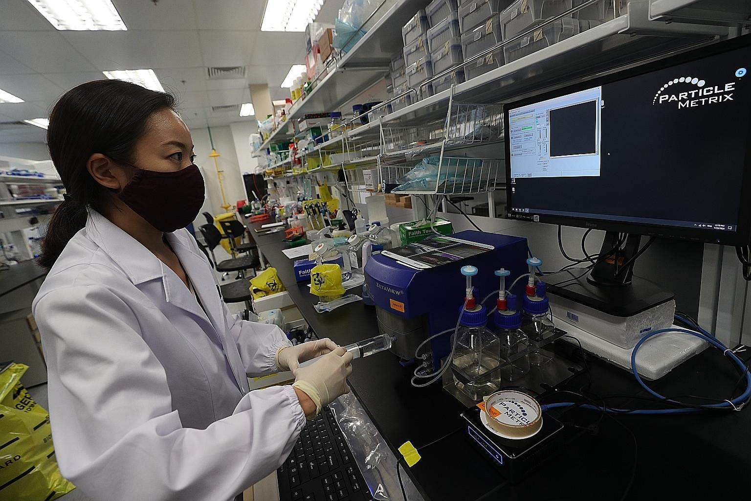 Carmine Therapeutics scientist Yumi Kawamura operating a device used to analyse extracellular vesicles, particles that are released by red blood cells. Carmine developed a technology that uses extracellular vesicles to deliver genes to parts of the b
