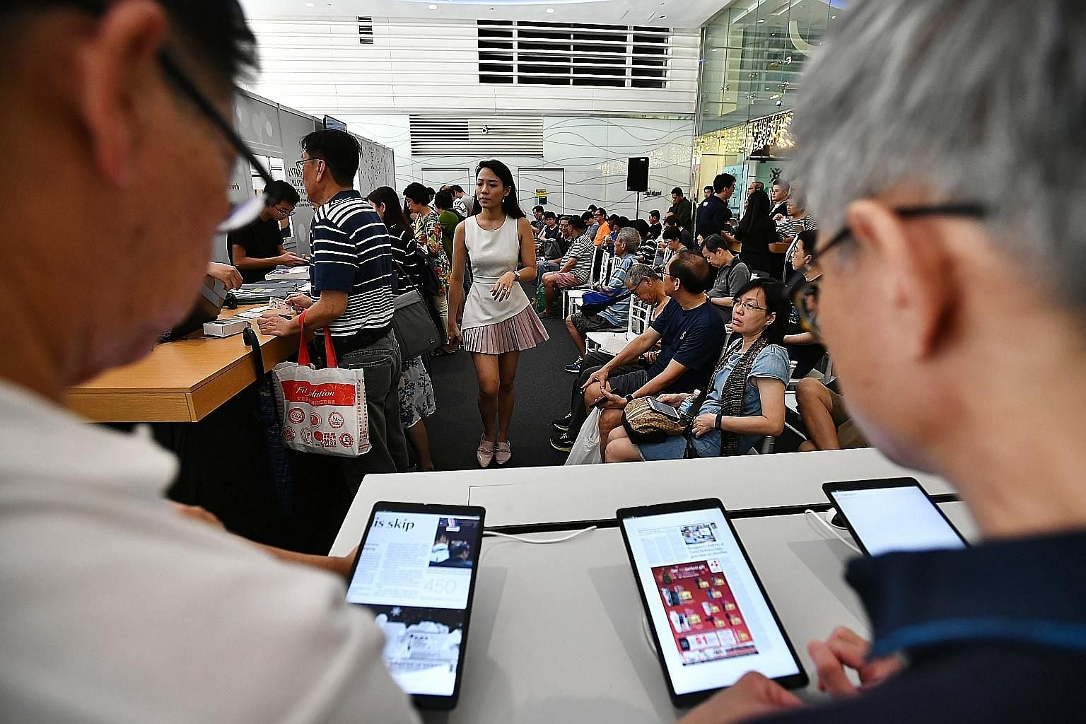Subscribers of The Straits Times waiting to collect the news tablet last December. Readers have given the news tablet, which offers the convenience of reading traditional print papers in a digital format, positive reviews. The ST Tab app is pre-insta