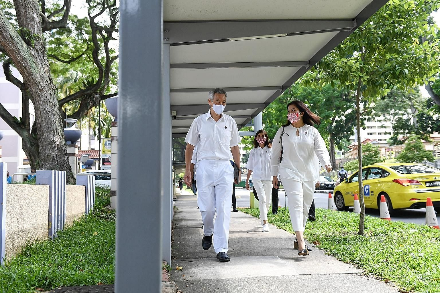 Prime Minister Lee Hsien Loong and fellow Ang Mo Kio GRC team member Nadia Ahmad Samdin on their way to Deyi Secondary School nomination centre yesterday. ST PHOTO: SHINTARO TAY