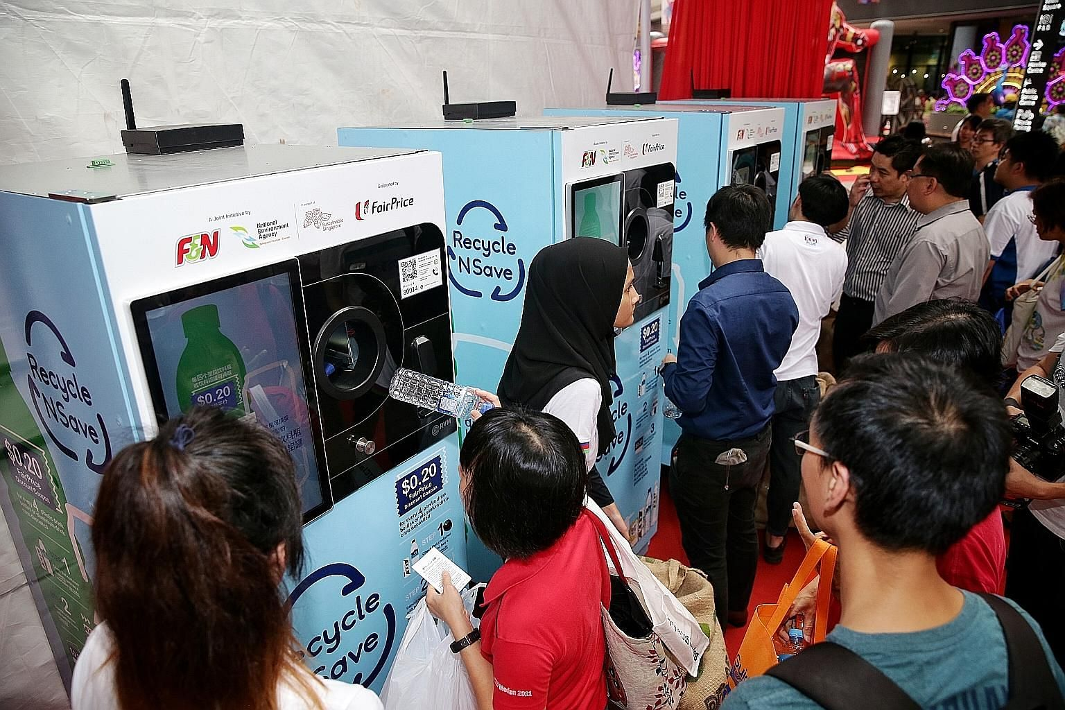 "The ""reverse"" vending machines during their launch at Our Tampines Hub last October. The older machines (above) dispense a 20-cent FairPrice discount voucher for every 20 containers deposited. The new machines offer more reward choices, including fre"