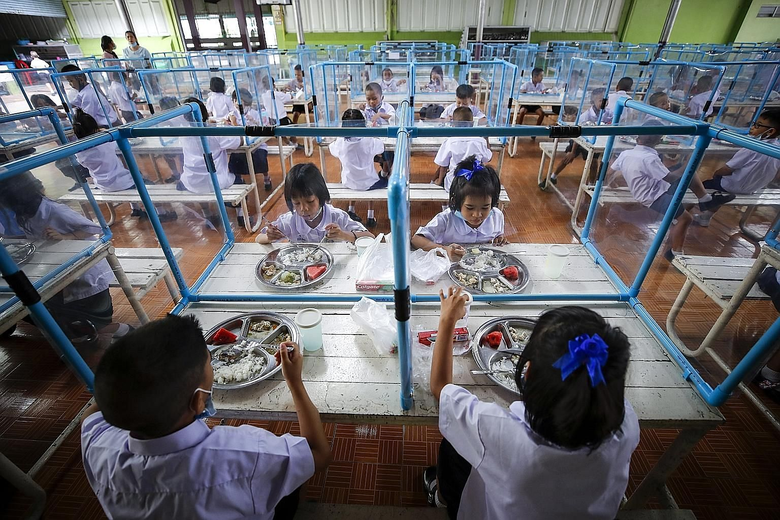 Students eating lunch together, separated by plastic sheets, at a school in Bangkok yesterday after months of distance learning.