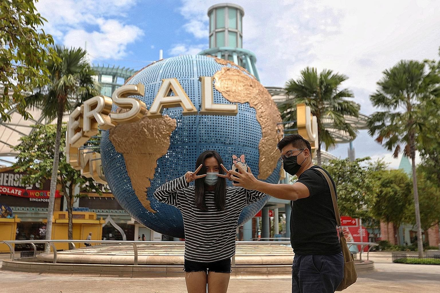 Left: Mr Joseph Teng, 31, and Ms Nu Mai Anh, 24, outside Universal Studios Singapore yesterday. With fewer visitors, they could enjoy some popular rides several times. Top: People waiting to get into the casino at Resorts World Sentosa yesterday. Abo