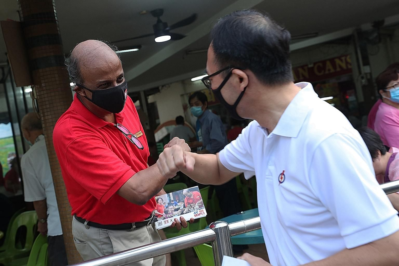 Singapore Democratic Party chairman Paul Tambyah and his rival Bukit Panjang SMC candidate Liang Eng Hwa of the People's Action Party greeting each other while meeting residents in Bangkit Road yesterday.