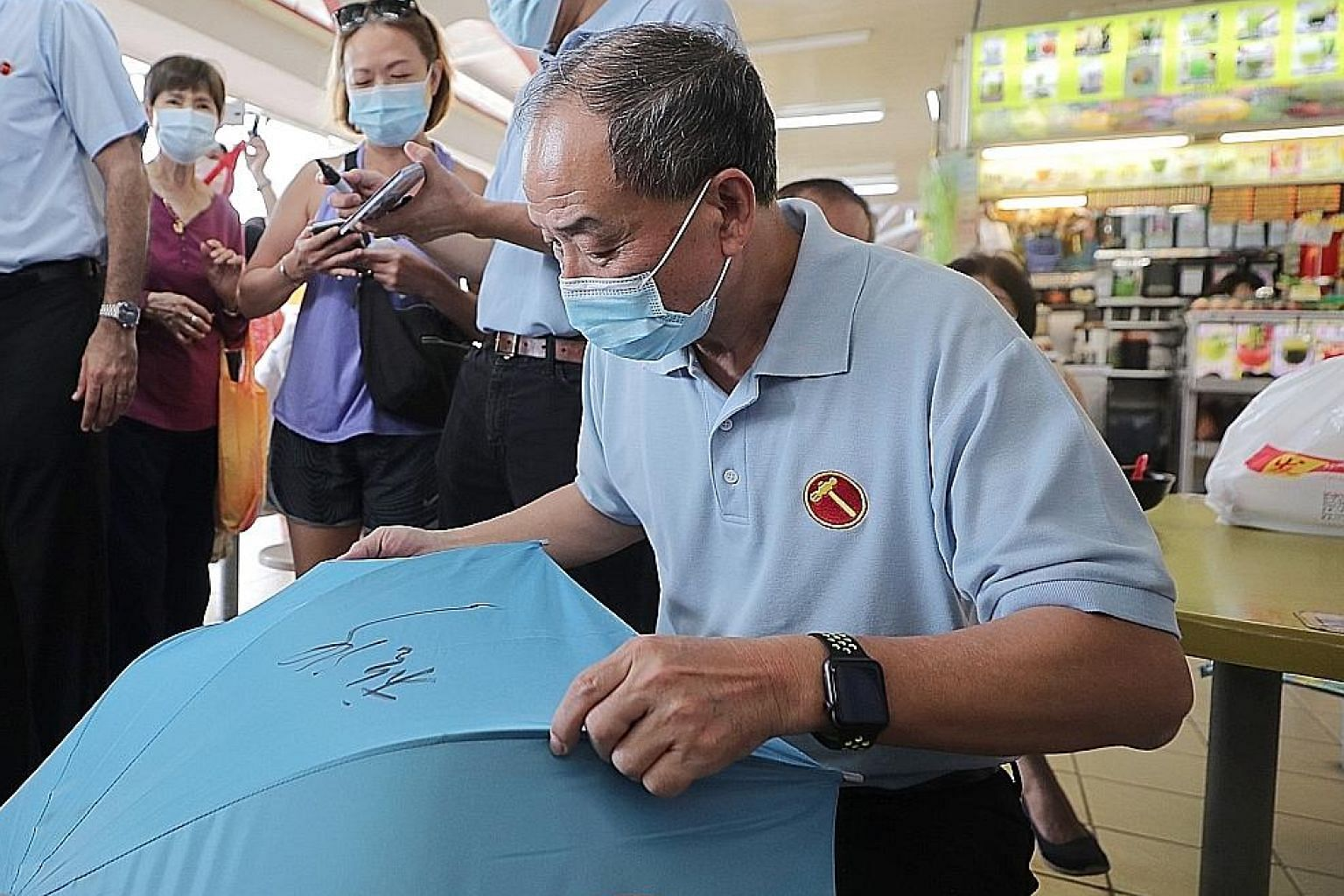 Former Workers' Party chief Low Thia Khiang, who is not standing in this election, autographing a WP umbrella during a visit to Kovan Hougang Market and Food Centre yesterday.