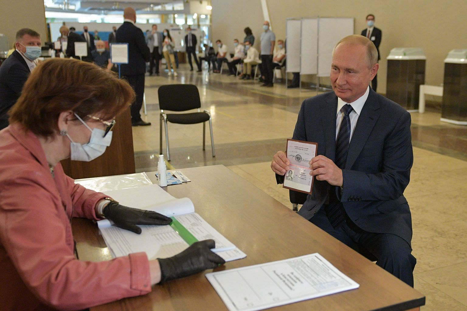 Russian President Vladimir Putin showing his passport to a member of a local electoral commission in Moscow ahead of casting his ballot in Wednesday's nationwide vote on constitutional reforms. The constitutional amendments were approved by just over