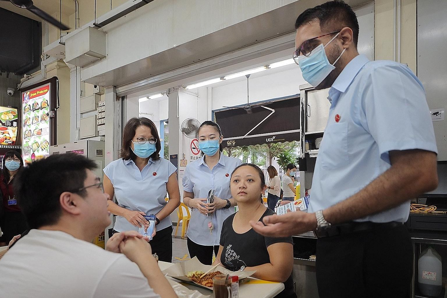 Workers' Party chief Pritam Singh, accompanied by party chairman Sylvia Lim (far left) and Punggol West SMC candidate Tan Chen Chen, chatting with customers at a coffee shop in Punggol Way yesterday.