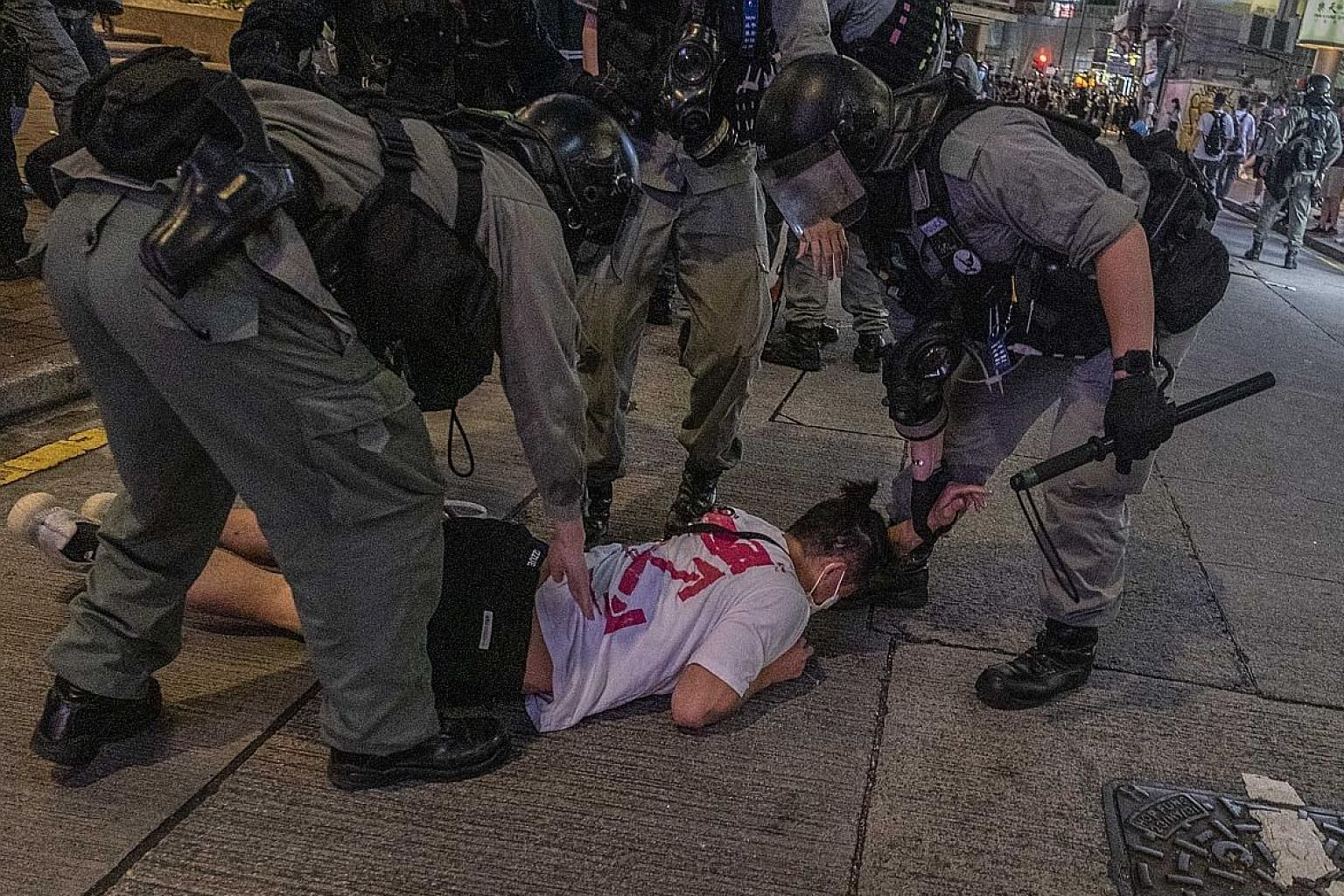 Police arresting a protester at a shopping area in the Causeway Bay area of Hong Kong last Wednesday. Hong Kong's economic environment has suffered greatly from the year-long social unrest, unstable foreign trade and the Covid-19 pandemic.