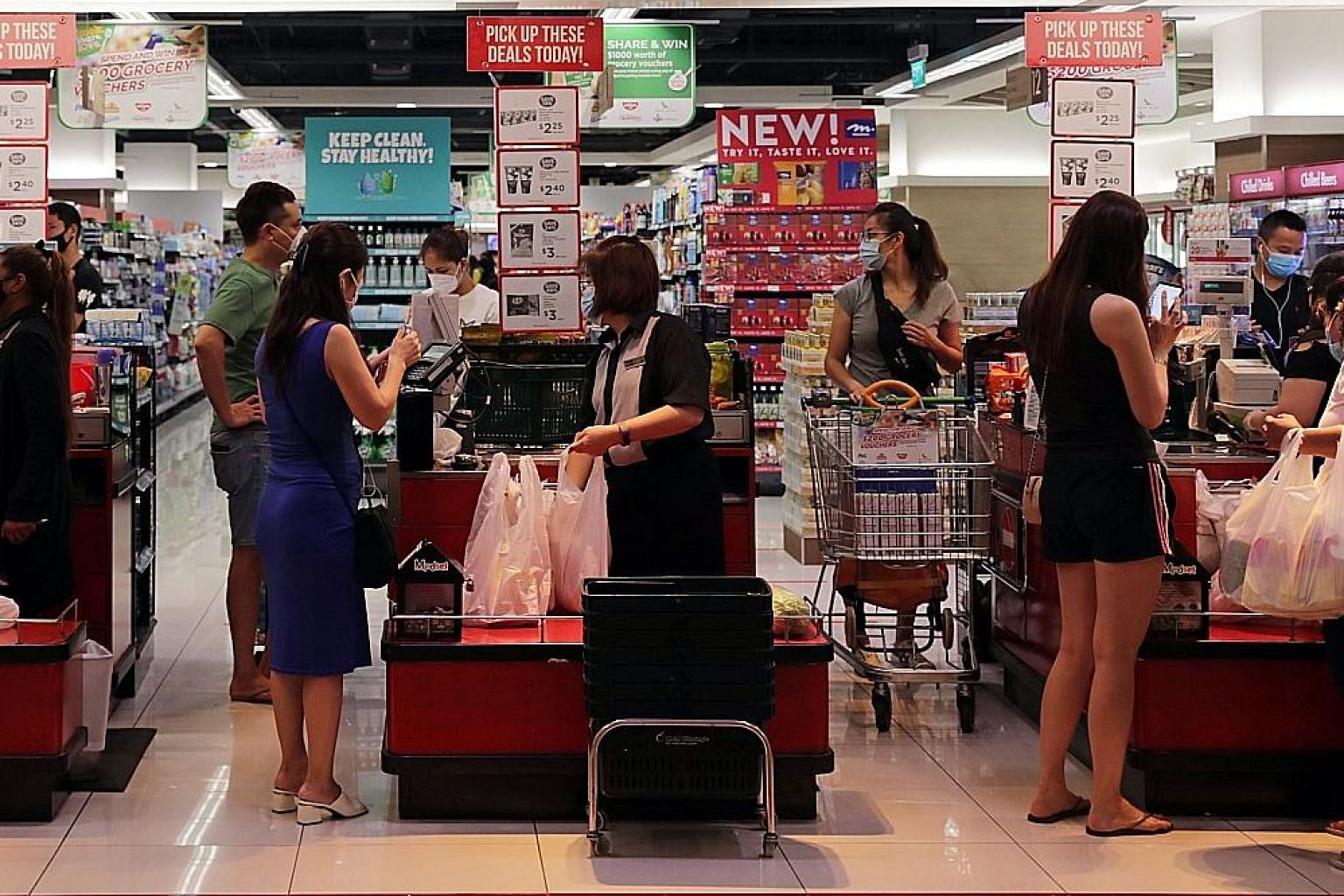Customers at the checkout section of a supermarket. Singapore's goods and services thttp://staff.straitstimes.com/node/706106/edit?content_lock_token=KPrL2IMW04fAERmwThxSlJF5M5Pa2vax is set to be raised from 7 per cent to 9 per cent between 2022 and 2025.