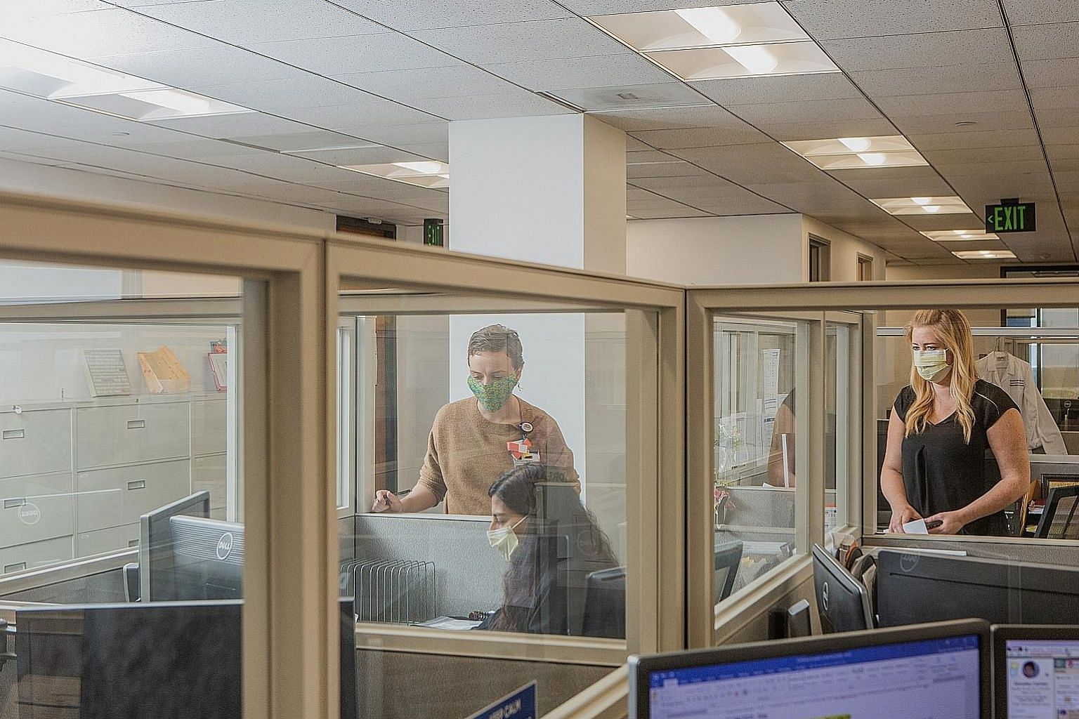 A California firm has replaced its open-plan office with protective barriers between cubicles. Kastle Systems, which designs and installs security systems for commercial buildings, has put in place a thermal camera (left) to measure temperatures and