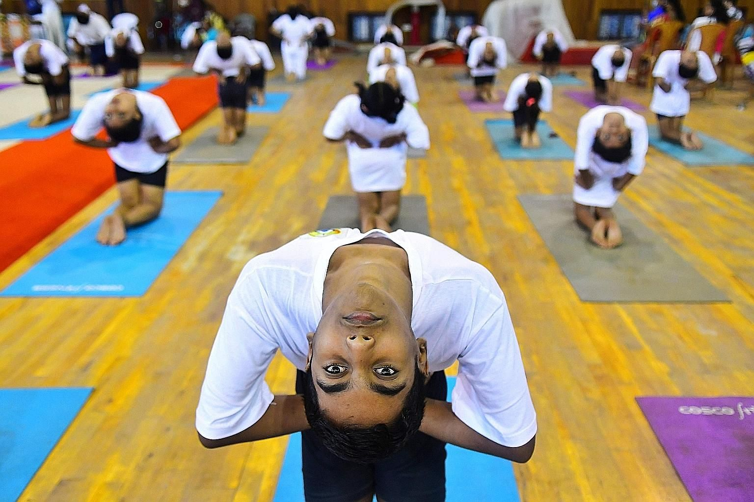 Students doing stretching exercises on International Yoga Day in Agartala, India, last month. PHOTO: AGENCE FRANCE-PRESSE