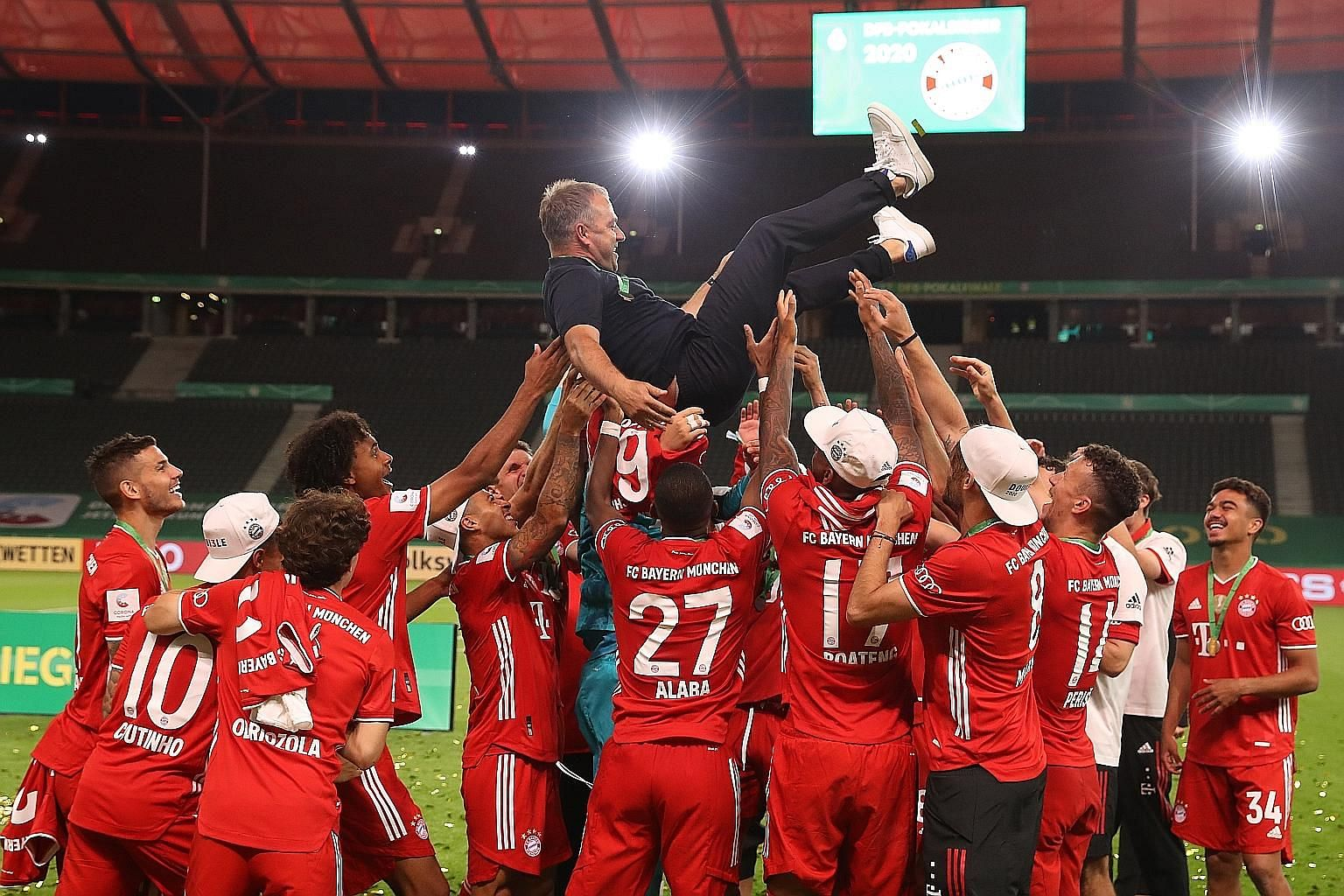 Bayern Munich coach Hansi Flick is tossed in the air by his players after they won the German Cup final against Bayer Leverkusen on Saturday.