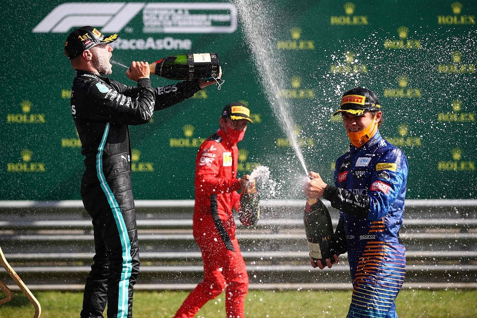 From left: Valtteri Bottas, Charles Leclerc and Lando Norris allowing themselves some liberal celebration with champagne after finishing on the podium in F1's delayed season-opener in Austria.