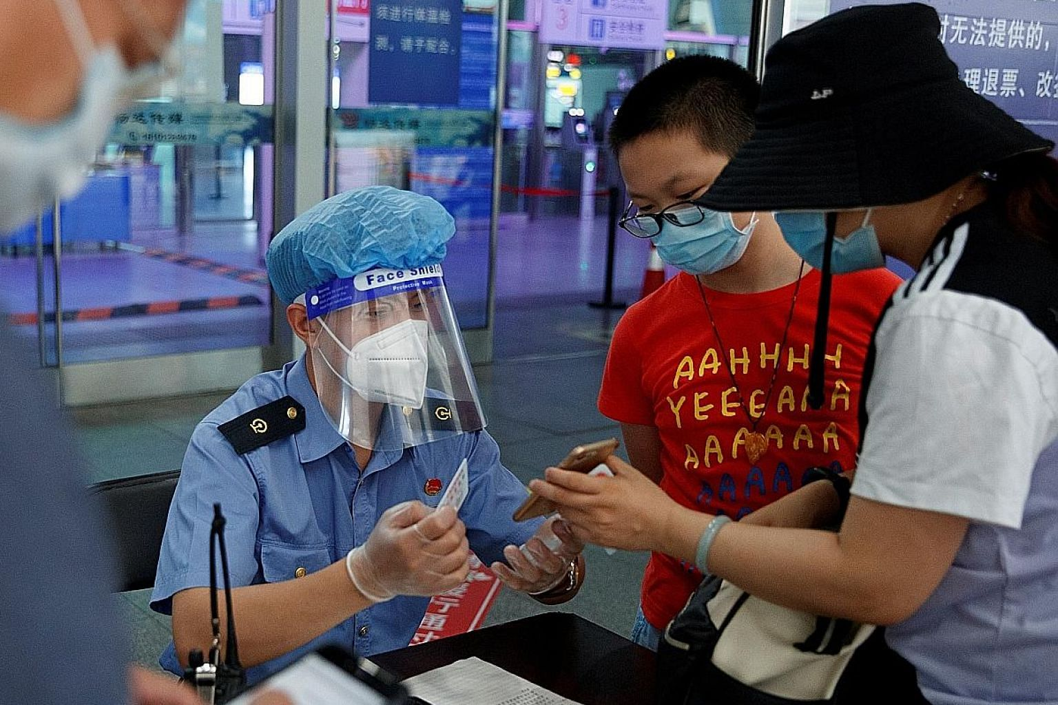 An employee checking the identity and health status of travellers before they enter the Beijing South Railway Station on Friday. PHOTO: REUTERS