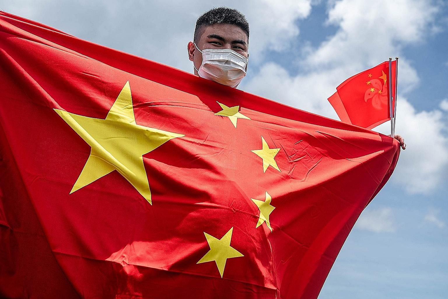 A Chinese government supporter holding the flags of China and Hong Kong to mark the passing of the new national security law. PHOTO: BLOOMBERG