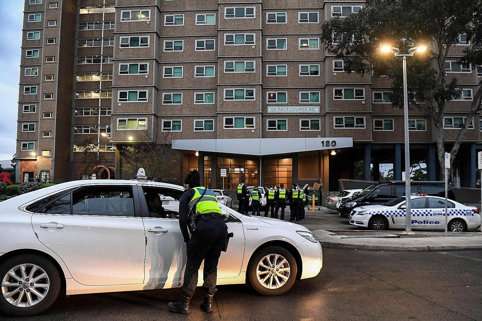 A woman (above) speaking to police officers yesterday after attempting to leave a public housing tower in Melbourne, the capital of the Australian state of Victoria. The police are enforcing a five-day lockdown of nine public housing towers (left) in