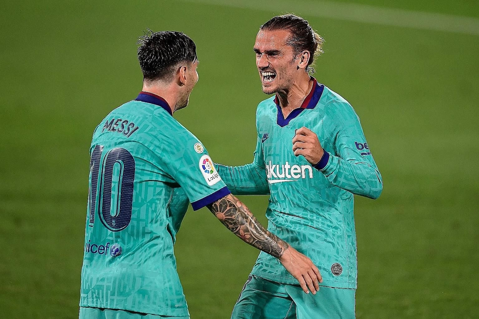 Antoine Griezmann celebrating with captain Lionel Messi after scoring against Villarreal on Sunday. Barcelona won 4-1 but trail Real Madrid by four points. PHOTO: AGENCE FRANCE-PRESSE