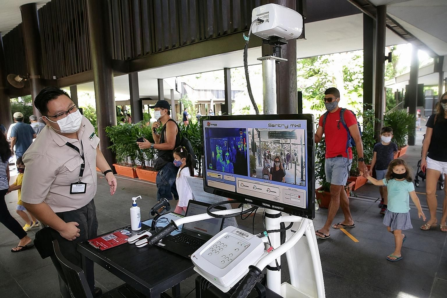 Visitors walking past a thermal scanner and checking in via SafeEntry yesterday before proceeding to the entrance of the Singapore Zoo, where they had their e-tickets scanned. Jurong Bird Park and the River Safari have also reopened, while the Night