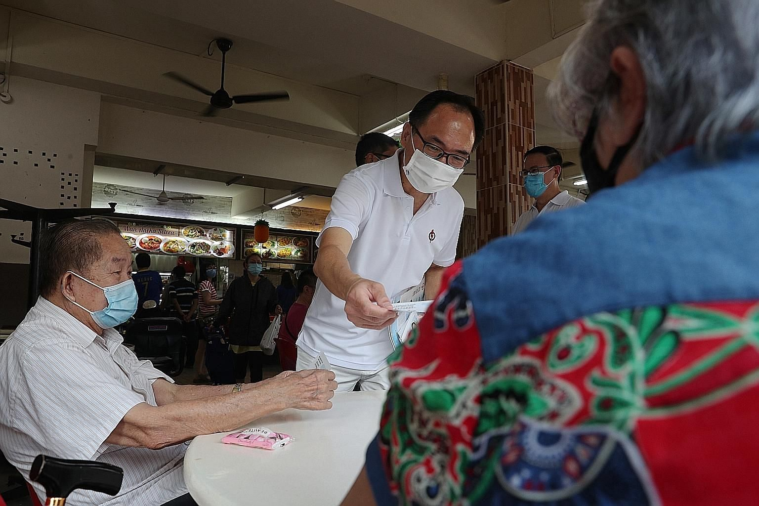 Mr Liang Eng Hwa, the PAP candidate for Bukit Panjang, giving out leaflets at Bangkit Market last Thursday. The managing director at DBS Bank is in a closely watched contest with Singapore Democratic Party chairman Paul Tambyah.
