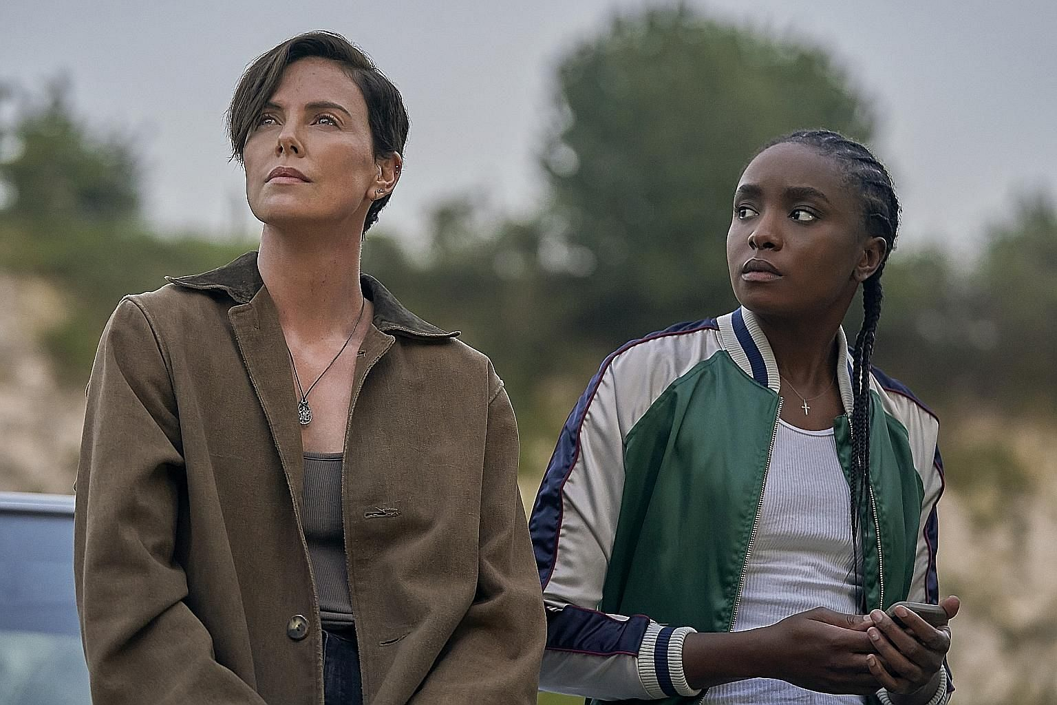 Keira Knightley (left) plays translator and linguist Katherine Gun in the biopic Official Secrets. Charlize Theron (above, left, with Kiki Layne) plays the leader of a secret clan of immortal warriors in The Old Guard.