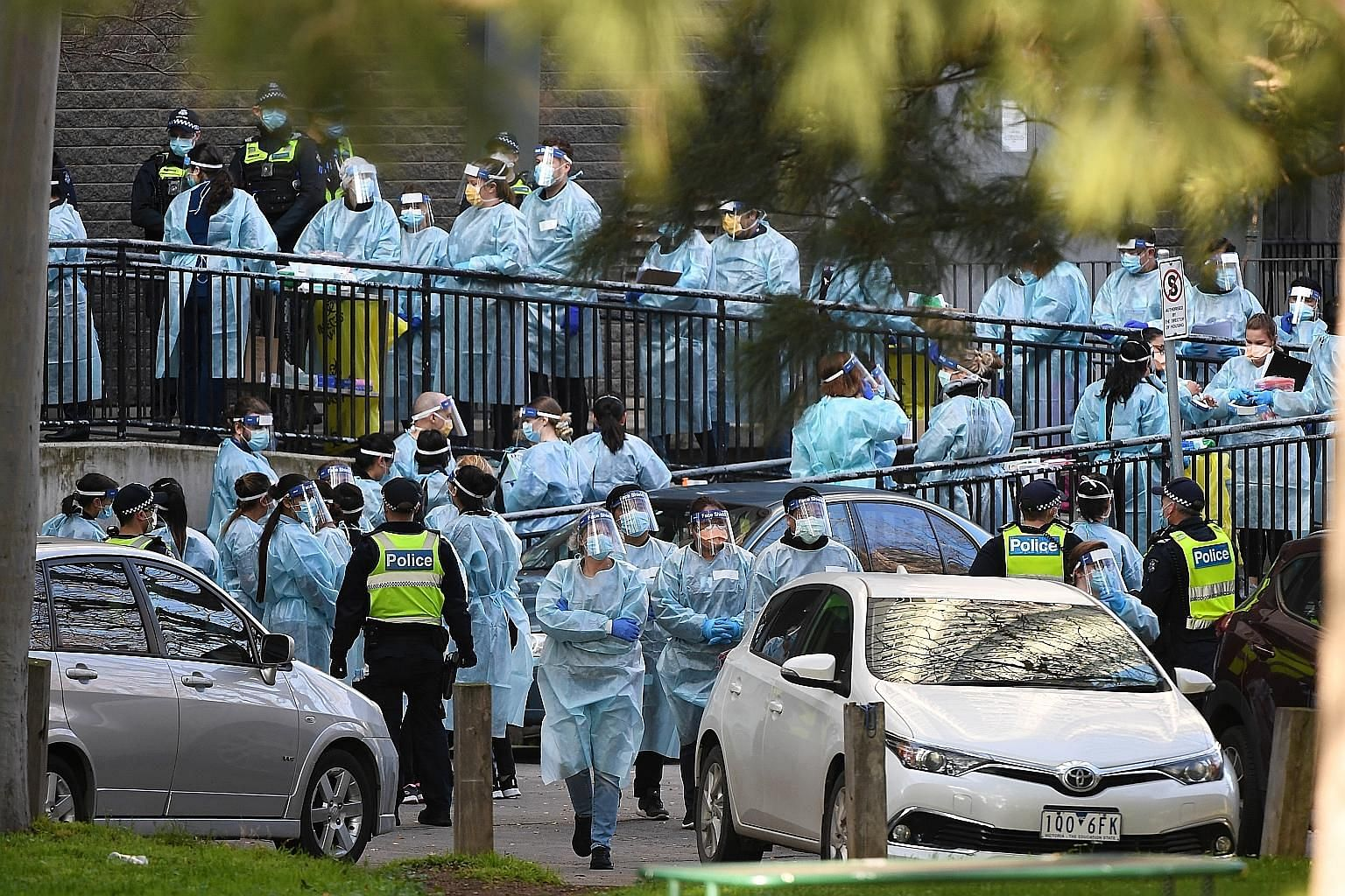 Above: Healthcare workers preparing to enter a public housing tower in North Melbourne yesterday. About 3,000 residents of such housing blocks in the city have been barred from leaving their flats. Far left: A support worker comforting a young child
