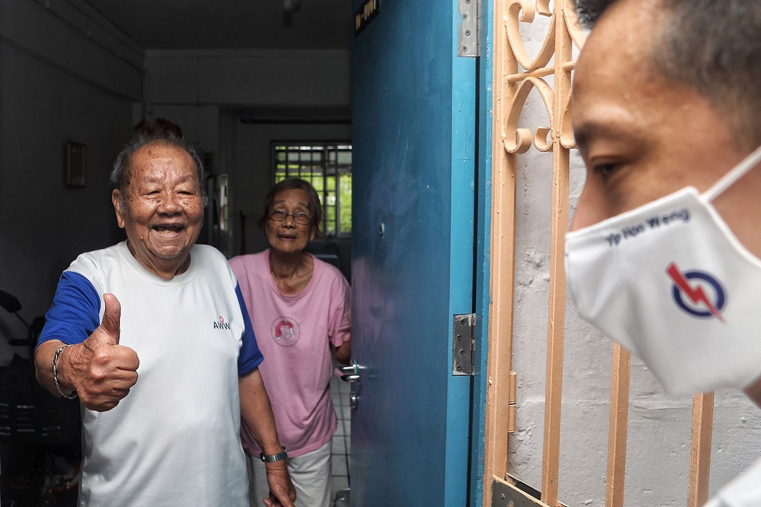 Mr Wong Win Cheong, 94, (with his 89-year-old wife Ho Sao Ning) giving Mr Yip Hon Weng the thumbs up during the People's Action Party candidate's walkabout at Block 123 Ang Mo Kio Avenue 6 yesterday.