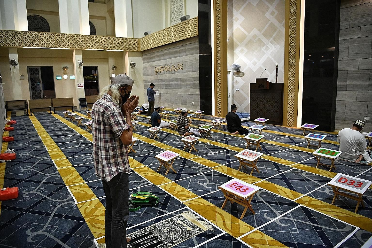Al-Ansar Mosque (above) in Bedok North was closed from the evening of Tuesday until Wednesday for cleaning and disinfection. It resumed prayer services yesterday (top), keeping to safe management measures like having worshippers pray in marked indivi