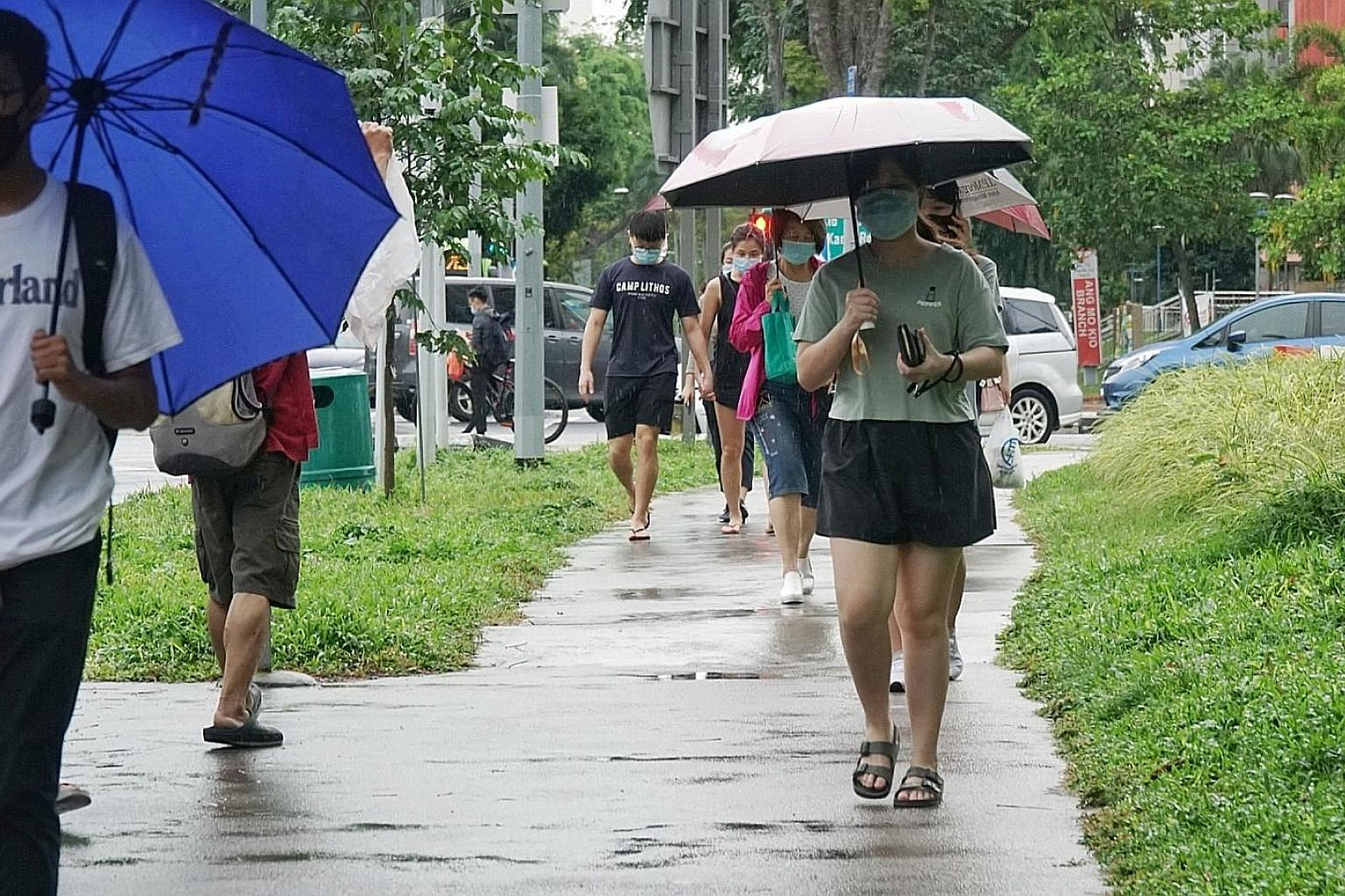Pedestrians along Ang Mo Kio Avenue 3 at around 6pm yesterday. Temperatures dipped to a low of between 22.9 deg C and 26 deg C. Daily midday temperatures had ranged between 28 deg C and 32 deg C for the past week. ST PHOTO: KHALID BABA