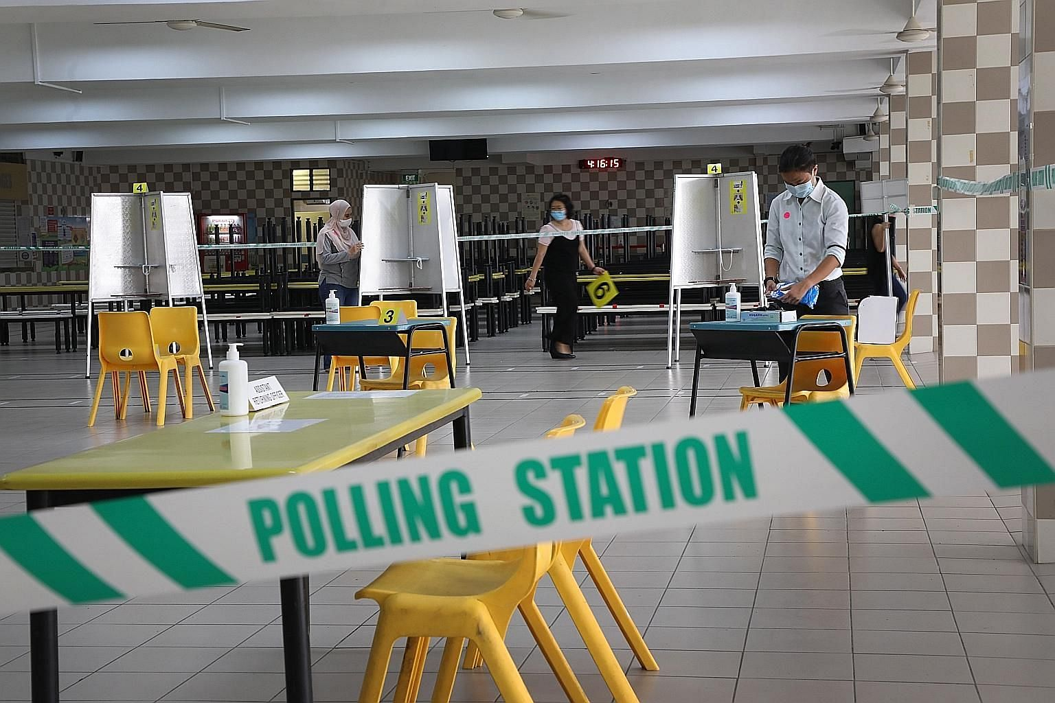 At Chung Cheng High School in Goodman Road yesterday, public servants set up the polling station, putting in place safe-distanced polling booths, temperaturetaking points, sanitising products and floor markings for spaced queues to ensure the safety