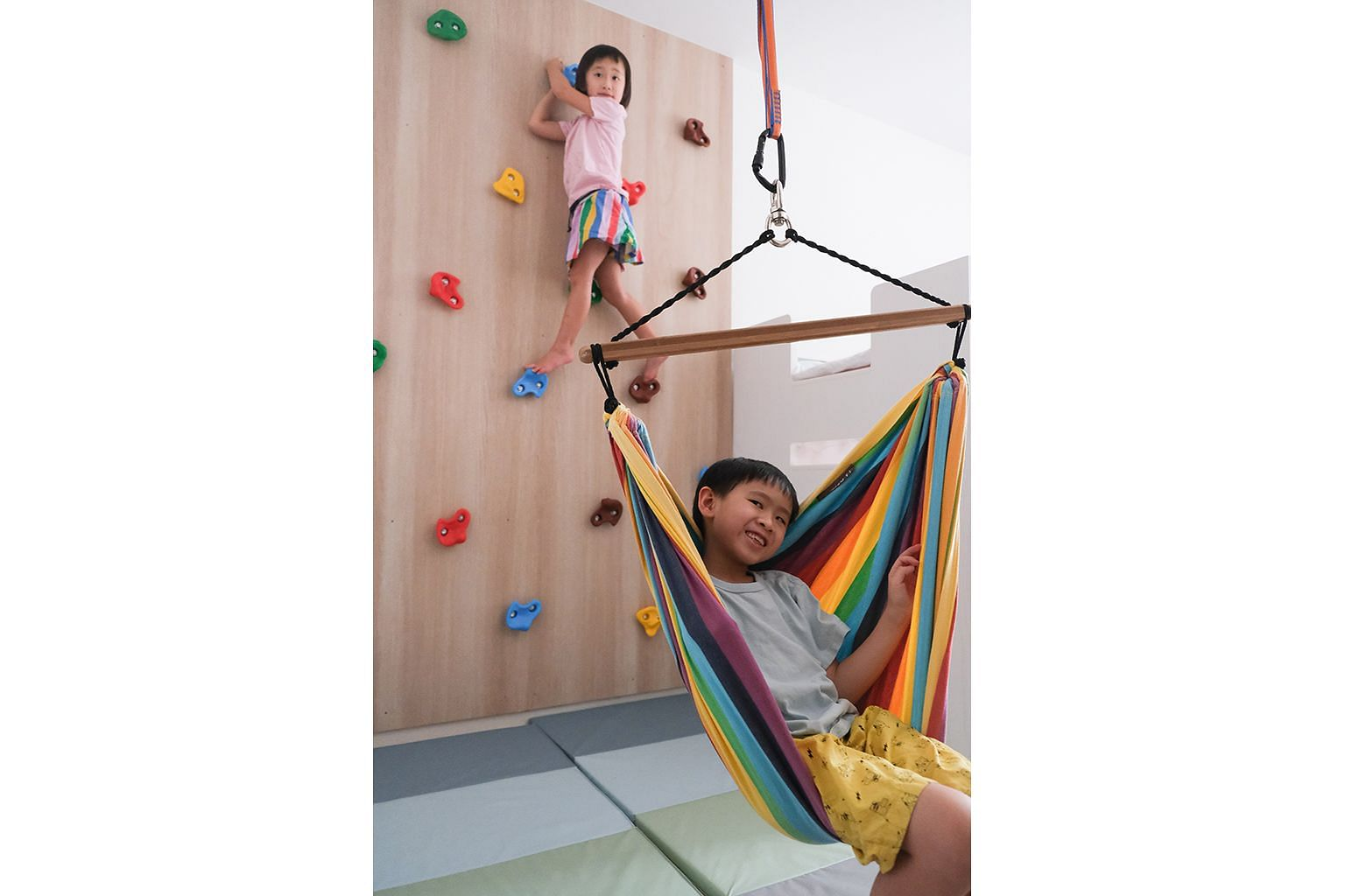 Ms Fynn Sor fitted a rock wall, a trapeze bar and a hammock swing in the room of her children, Riley and Zachary.