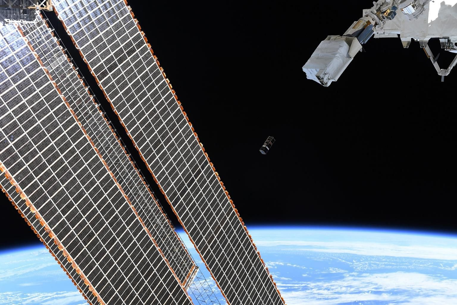 SpooQy-1 being ejected from the Japanese Small Satellite Orbital Deployer past the International Space Station's (ISS) solar arrays. This Nasa photograph was taken by an astronaut on the ISS.