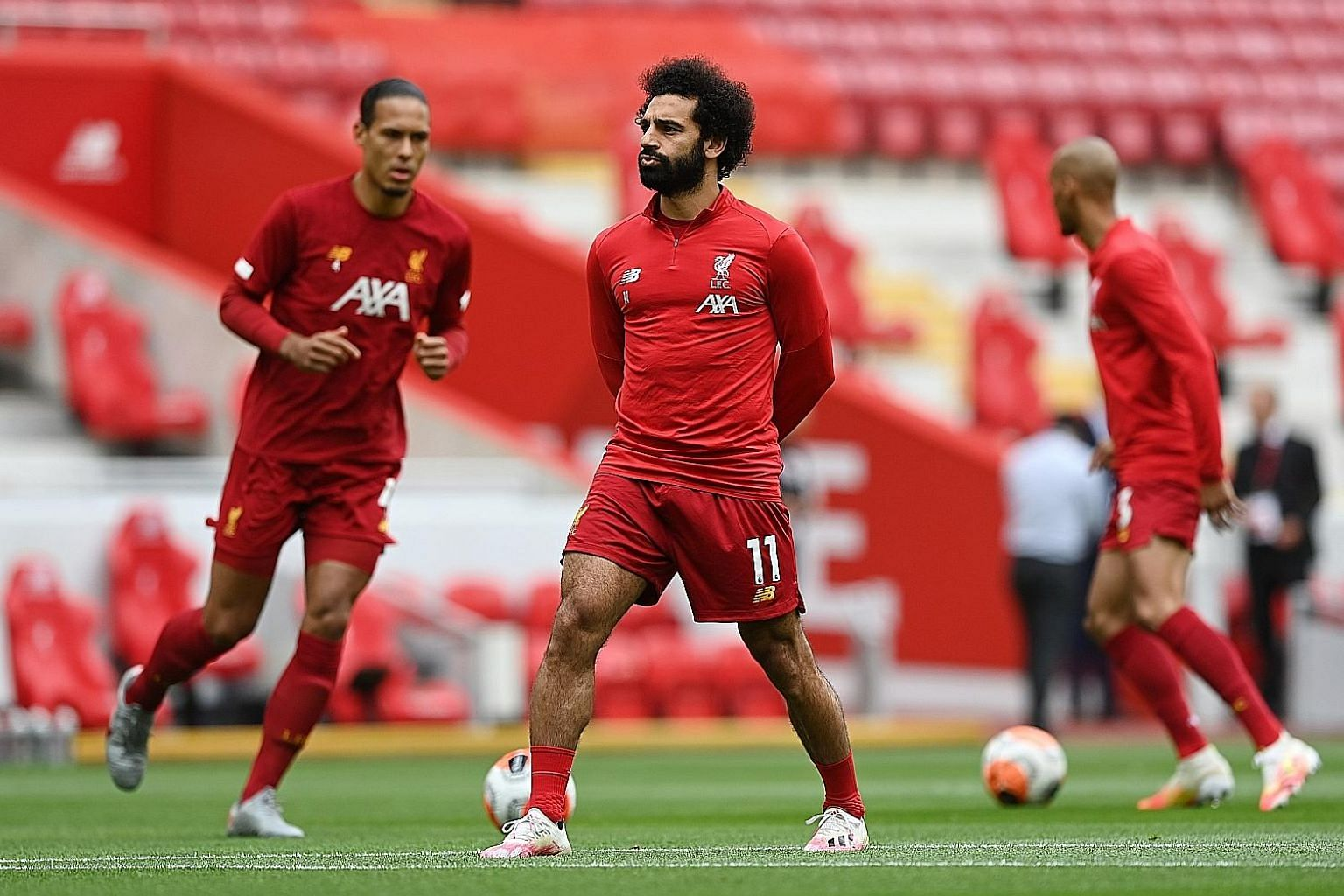 Right: Liverpool's Virgil van Dijk and Mohamed Salah warming up before a match. The Egyptian star is one of the key contributors to the Reds' first English title in 30 years. Below: Liverpool manager Jurgen Klopp addresses the media at a virtual pres