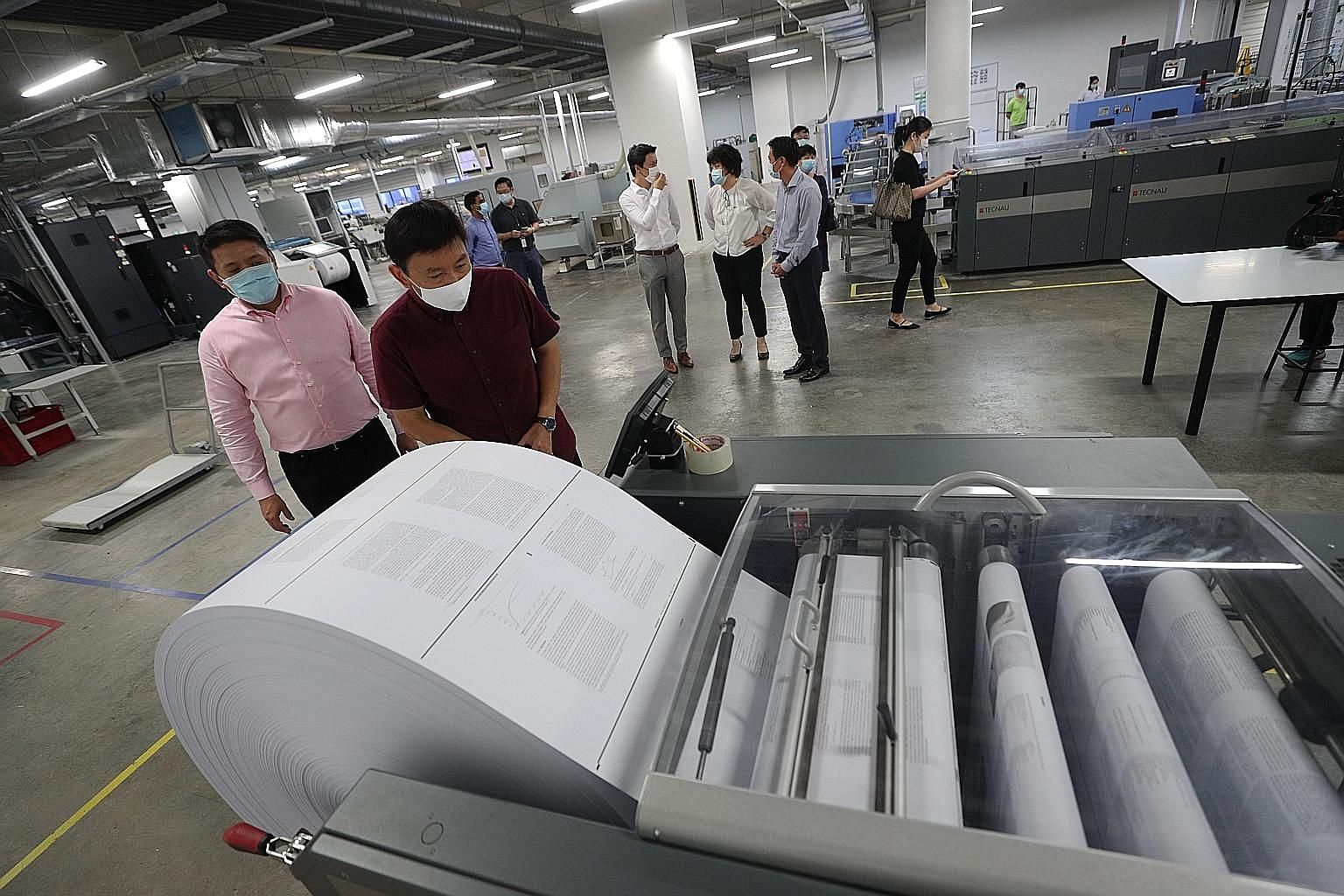 Senior Minister of State for Trade and Industry Chee Hong Tat checking out the printing process at Markono Content Solutions' facility in Pioneer yesterday as the company's managing director Edwin Ng looked on. ST PHOTO: TIMOTHY DAVID