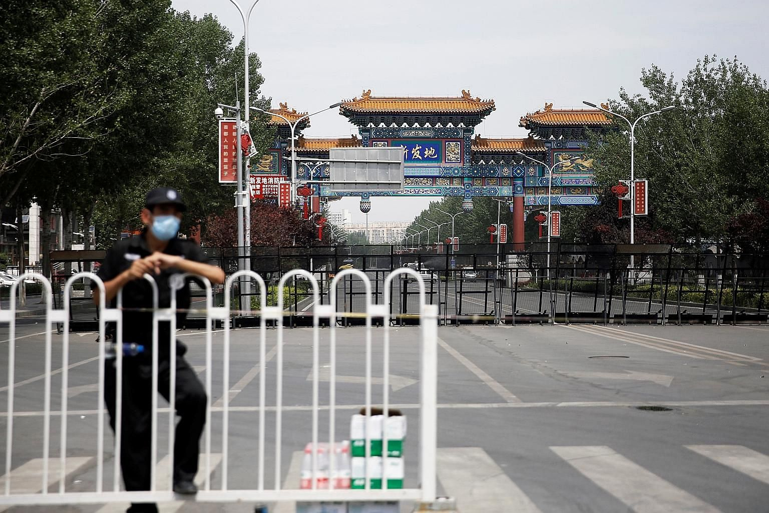 A security officer at the blocked entrance to the Xinfadi wholesale market in Beijing on June 16. When the first case there was detected on June 11, Beijing swiftly closed the market, which houses some 8,000 stallholders and workers and is visited by