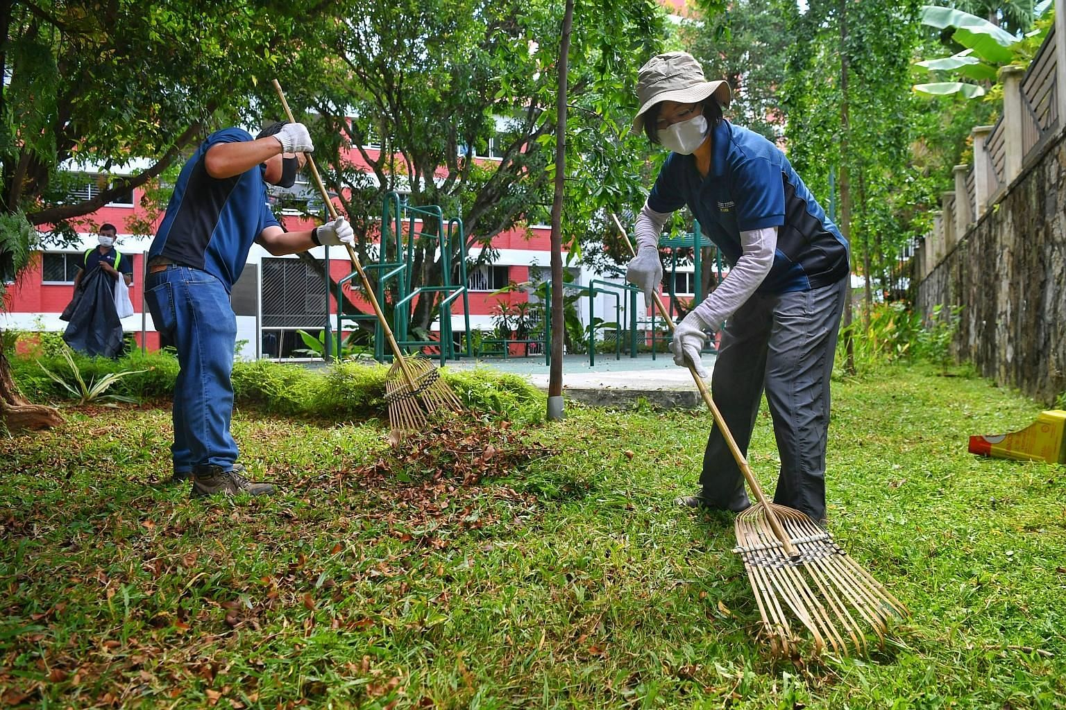 """Senior Minister of State Sim Ann (right), who is an MP for Holland-Bukit Timah GRC, helping to clear the grass after it was cut by migrant workers who volunteered their time yesterday. Ms Sim said: """"I was very touched... that they are willing to come"""