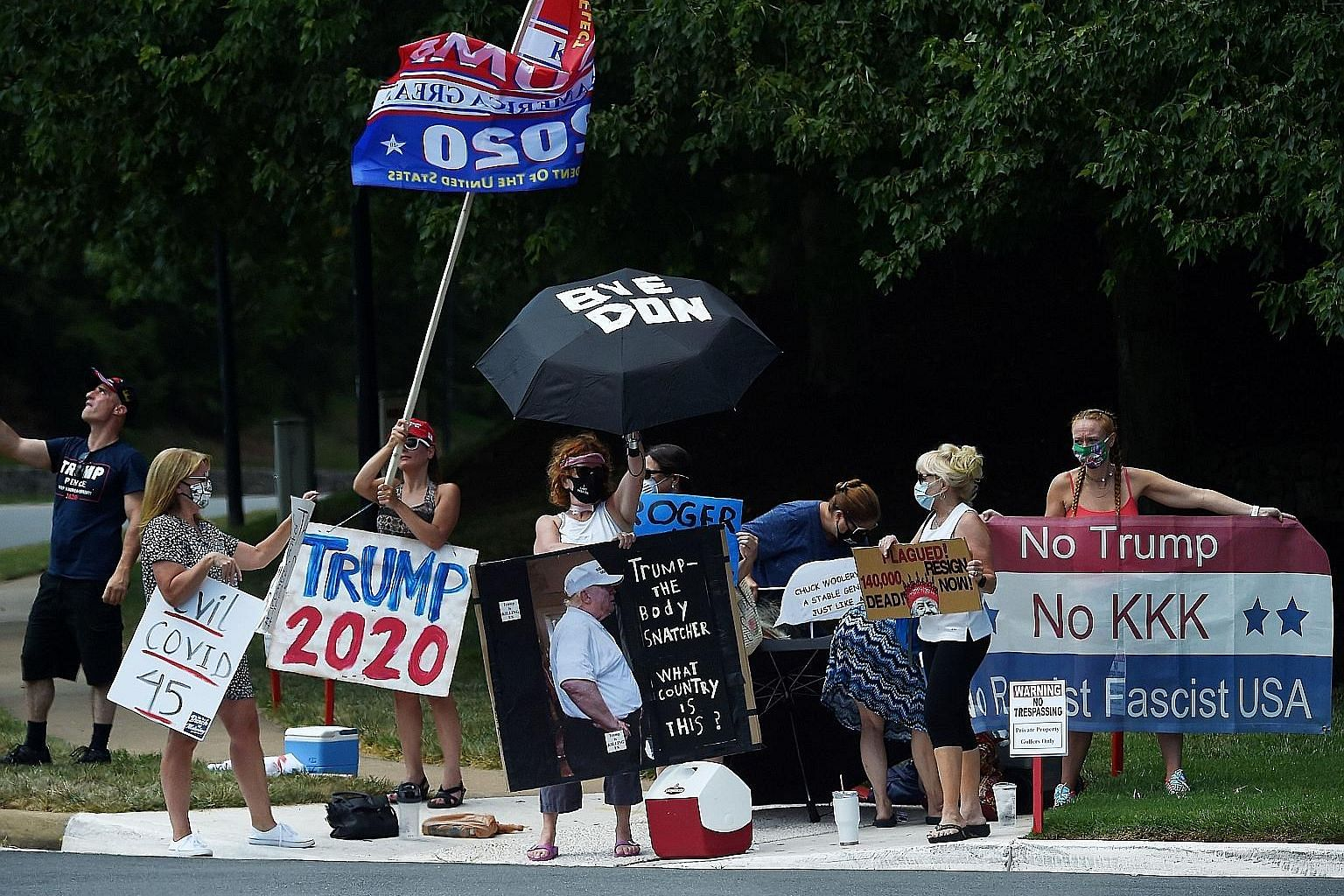 Protesters and supporters of US President Donald Trump sending their respective messages outside the Trump National Golf Club in Sterling, Virginia, on Sunday.
