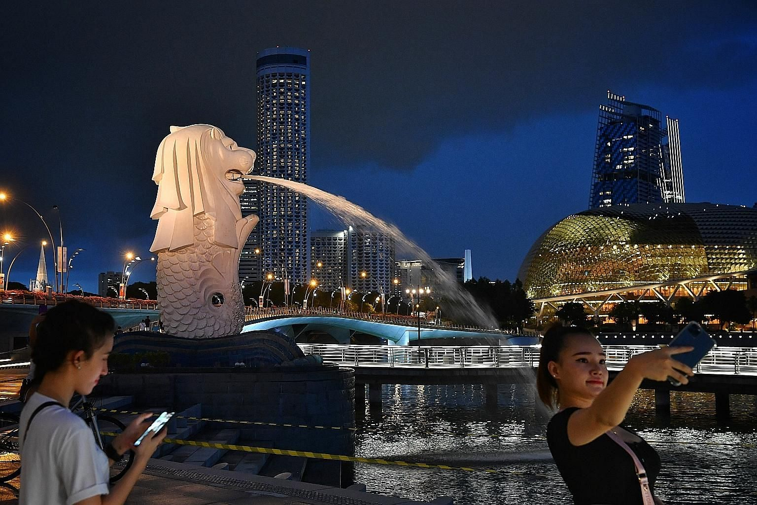 Visitors at Merlion Park (above) last month and shoppers at Raffles City Shopping Centre (left) yesterday. The newly launched $45 million campaign aims to help prop up tourism-dependent businesses with local demand.