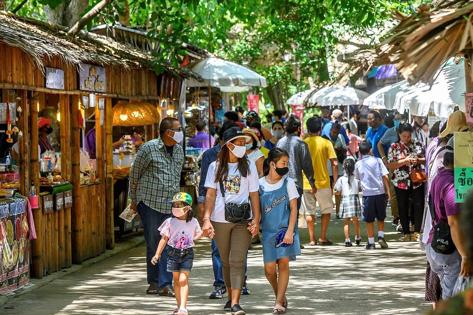 Local tourists at a market outside Ayutthaya, north of Bangkok, last Saturday. Over the past two months, Bangkok has lifted its night curfew and eased curbs on inter-provincial travel to aid its economy.