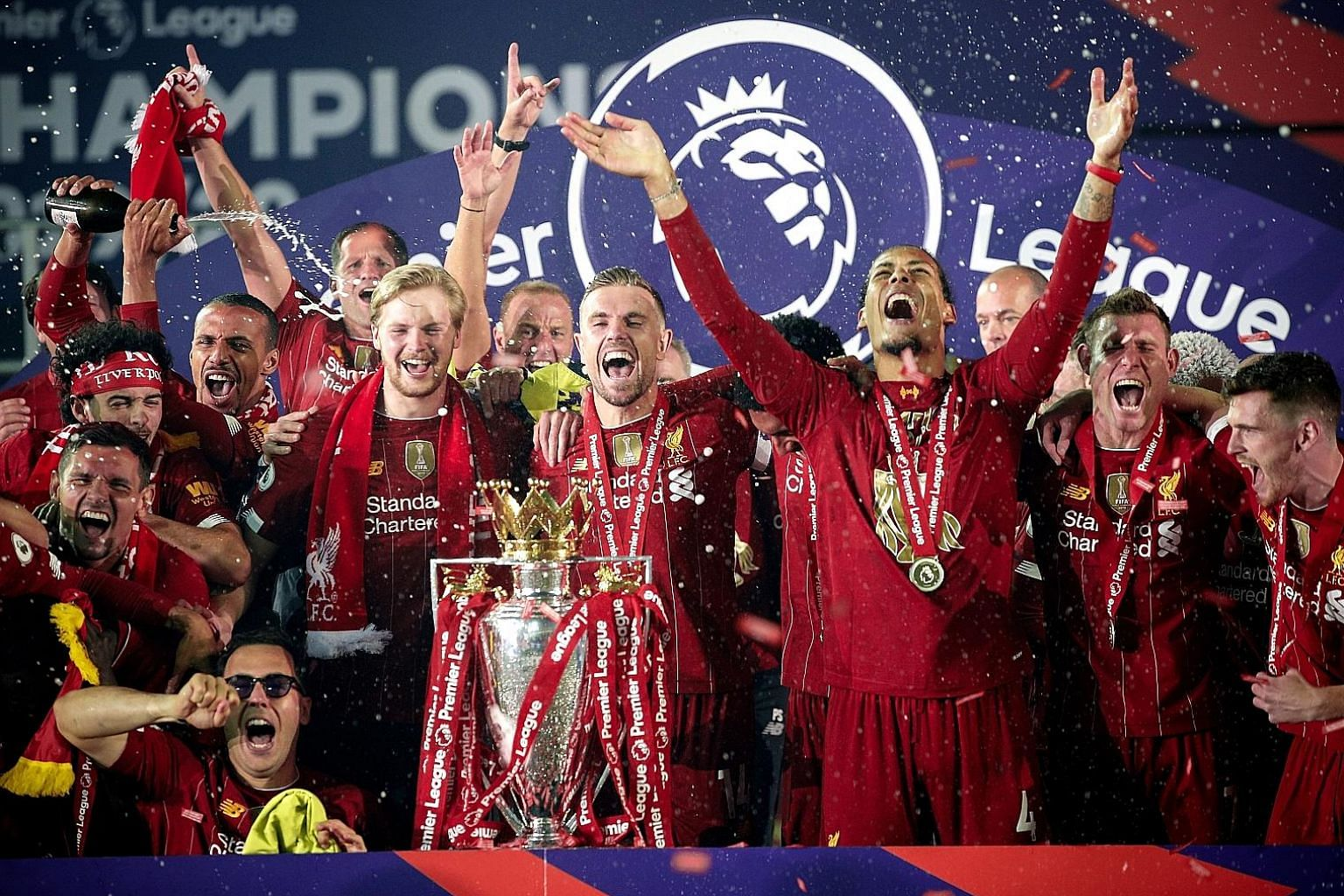 Skipper Jordan Henderson (centre) and teammates cheering with the Premier League trophy after the presentation at Anfield on Wednesday. Top: The Premier League trophy is manager Jurgen Klopp's fourth with Liverpool in a year after the Uefa Super Cup,