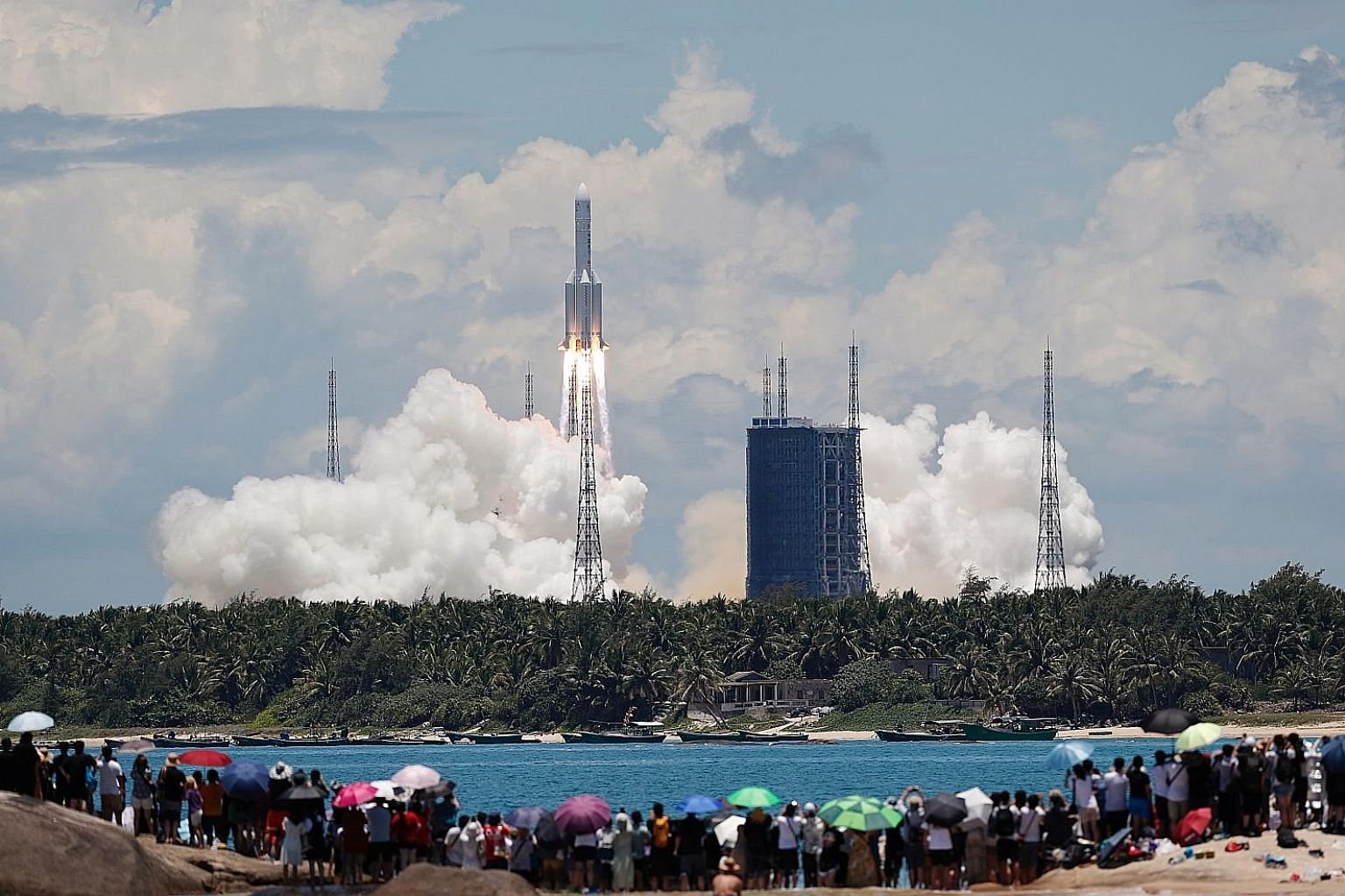 A crowd of onlookers watching from a beach as the Long March 5 Y-4 rocket, carrying the unmanned Tianwen-1 probe, blasted off on its Mars mission yesterday. This photo from China Daily shows the rocket launch at the Wenchang Space Launch Centre on Ch