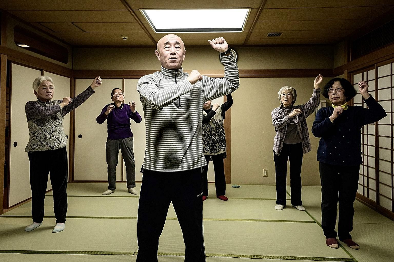 Judo therapist Taisuke Kasuya leading seniors in judo-based exercises at a community centre in Tokyo.