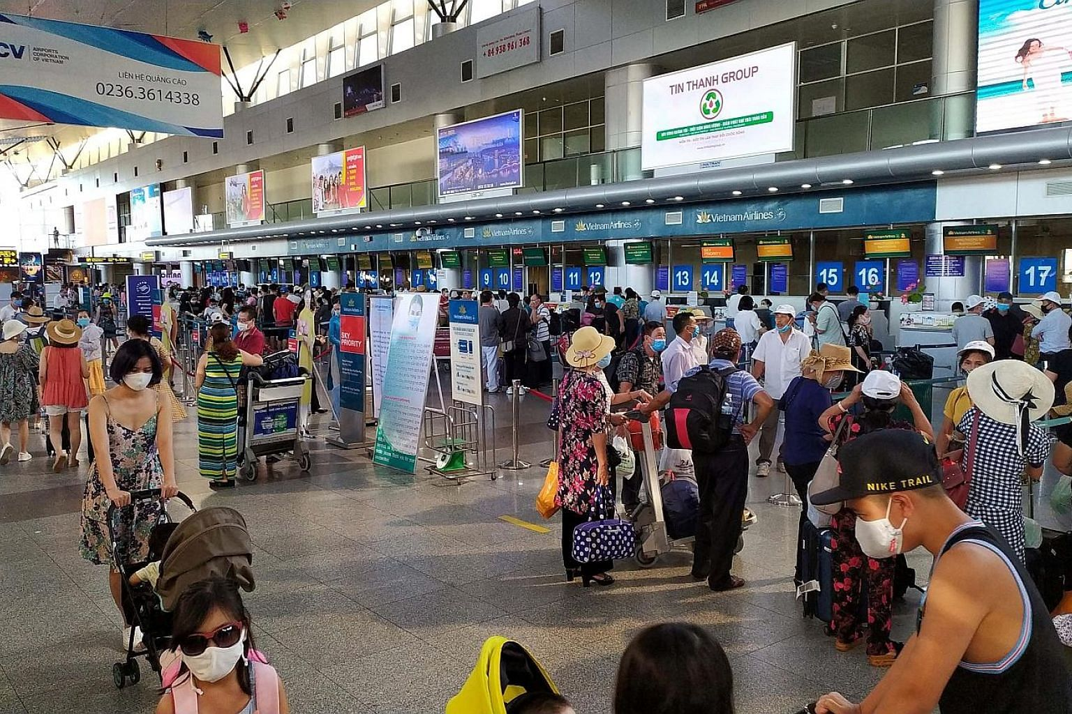 Domestic tourists in protective masks waiting to check-in for departure at Danang's airport on Sunday, as Vietnam imposed new measures to halt the spread of Covid-19. PHOTO: REUTERS