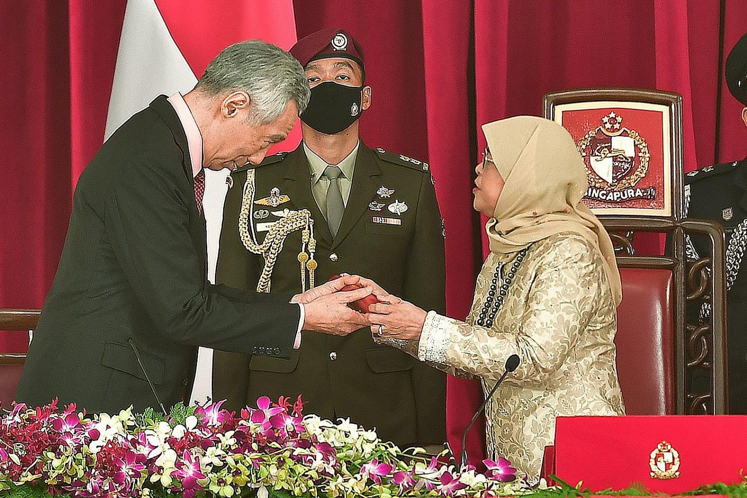 Prime Minister Lee Hsien Loong receiving the instrument of appointment from President Halimah Yacob at the Istana yesterday, during the swearing-in ceremony for the Prime Minister and other Cabinet ministers. ST PHOTO: DESMOND WEE